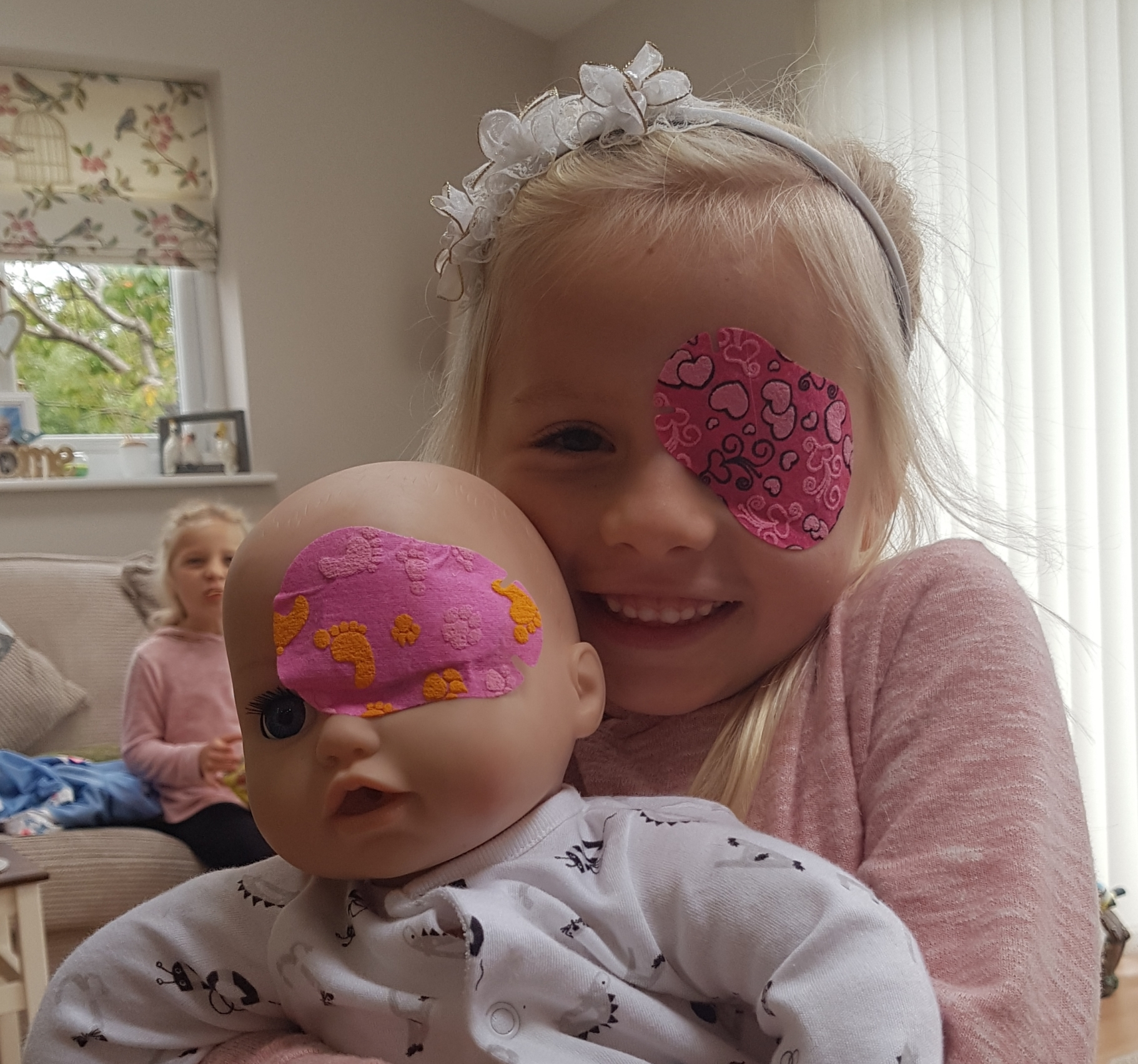 Patient of Manchester Royal Eye Hospital Jess and her doll with matching eye patches